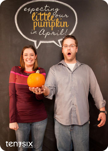 Man & Woman holding pumpkin for pregnancy announcement